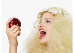 手拿苹果的浓妆金发女孩图片