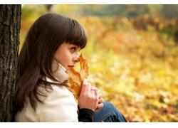 手拿枫叶的女孩图片