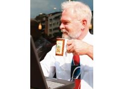 电脑旁喝咖啡的老人图片