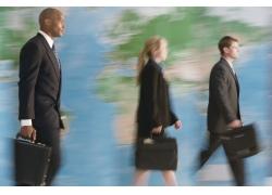 世界地图前行走的外国商务人士高清图片
