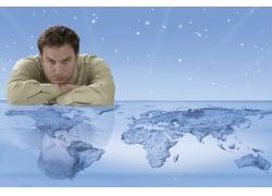 趴在世界地图上的外国商务男性高清图片