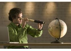 用望远镜观看地球仪的商务男性高清图片