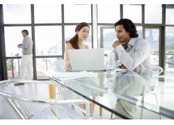 笔记本电脑旁商讨的外国男女高清图片
