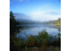 蓝天下山林中的河水图片