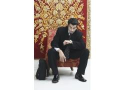 坐在椅子上看时间的商务男士图片