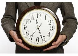商务人士双手托着钟表高清图片