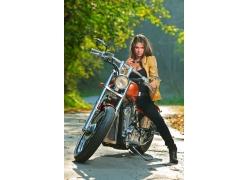 骑在摩托车上手拿墨镜的美女高清图片