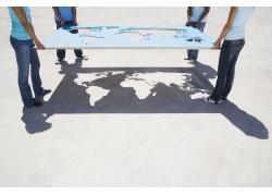 四个人手拿镂空地图摄影图片
