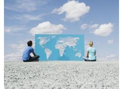 坐在地上的外国人与镂空世界地图