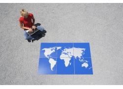 玩电脑的外国女人与地图拼图