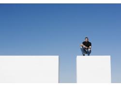 蹲在高处的外国男人图片