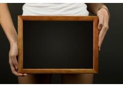 拿黑色相框的人物图片