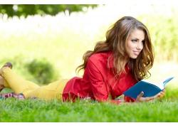 趴在草地上看书的外国美女图片