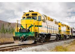 蓝天白云下一辆驶过来的黄皮绿条纹火车