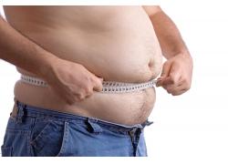 胖男人正在用米尺量肚子
