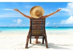 坐在椅子上在沙滩上晒太阳的美女背影