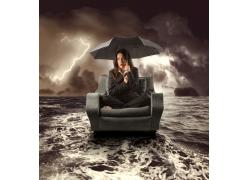 坐在沙发上打着伞的外国女人