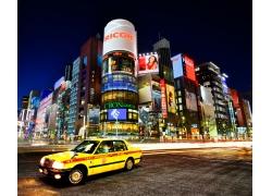 行驶在高楼中间的出租车夜景图片