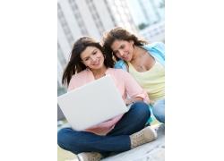 坐着看笔记本的两位美女