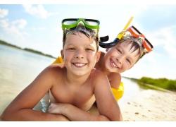 趴在沙滩上玩耍的小男孩