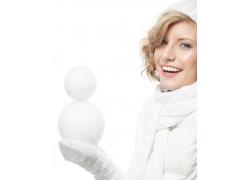 拿两个雪球的冬天女孩图片