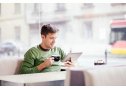 喝咖啡看平板电脑的男人