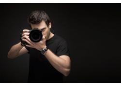 黑色背景下正在拍照的男摄影师