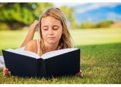 趴在草地上看书的女孩图片